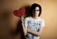 Hombre joven con un corazón en manos Fotos de archivo libres de regalías