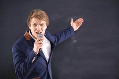 Hombre joven con un micrófono durante la presentación de la energía Foto de archivo libre de regalías