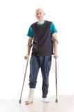 Hombre joven con un molde y las muletas de la pierna Fotografía de archivo