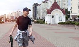 Hombre joven con un monopatín en una calle de la ciudad Fotos de archivo