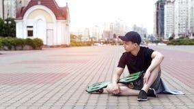 Hombre joven con un monopatín en una calle de la ciudad Fotografía de archivo