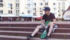 Hombre joven con un monopatín en una calle de la ciudad Foto de archivo