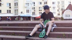 Hombre joven con un monopatín en una calle de la ciudad Imagenes de archivo