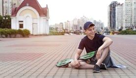Hombre joven con un monopatín en una calle de la ciudad Fotos de archivo libres de regalías