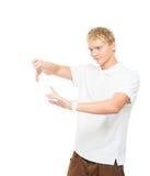 Hombre joven con un objeto imaginario aislado en blanco Imágenes de archivo libres de regalías
