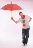Hombre joven con un paraguas rojo fotografía de archivo