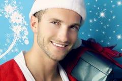 Hombre joven con un regalo de la Navidad Foto de archivo libre de regalías