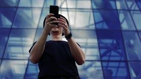 Hombre joven con un smartphone almacen de video