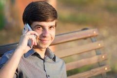 Hombre joven con un smartphone en el banco Fotos de archivo libres de regalías
