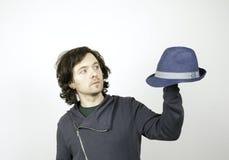 Hombre joven con un sombrero azul a disposición en un fondo blanco Fotografía de archivo libre de regalías