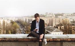 Hombre joven con un teléfono en el tejado de un edificio Fotos de archivo libres de regalías