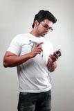 Hombre joven con un teléfono móvil Imagenes de archivo