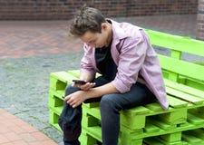 Hombre joven con un teléfono que se sienta en un banco Imagen de archivo libre de regalías