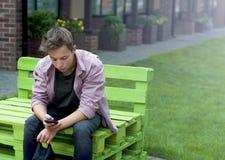 Hombre joven con un teléfono que se sienta en un banco Foto de archivo libre de regalías