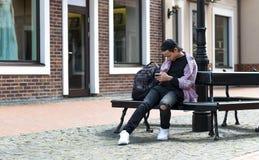 Hombre joven con un teléfono que se sienta en un banco Imagen de archivo