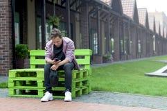 Hombre joven con un teléfono que se sienta en un banco Fotografía de archivo libre de regalías