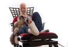 Hombre joven con un tobillo quebrado y un molde de la pierna Foto de archivo libre de regalías