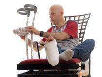 Hombre joven con un tobillo quebrado y un molde de la pierna Imagenes de archivo