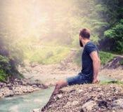 Hombre joven con una barba y pelo corto, sentándose en el banco de un río de la montaña en pantalones cortos y una camisa azul, c Fotos de archivo libres de regalías