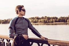Hombre joven con una bicicleta cerca del río Imágenes de archivo libres de regalías