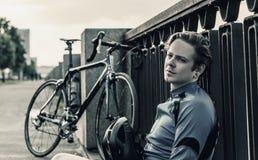 Hombre joven con una bicicleta cerca del río Fotos de archivo libres de regalías