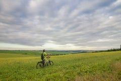 Hombre joven con una bicicleta en campo verde en un día de verano soleado Foto de archivo