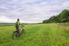 Hombre joven con una bicicleta en campo verde en un día de verano soleado Fotos de archivo