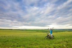 Hombre joven con una bicicleta en campo verde en un día de verano soleado Imagen de archivo libre de regalías