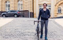Hombre joven con una bicicleta en una calle de la ciudad Foto de archivo