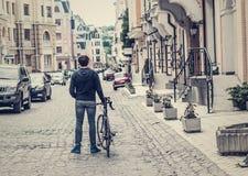 Hombre joven con una bicicleta en una calle de la ciudad Imagen de archivo