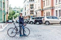 Hombre joven con una bicicleta en una calle de la ciudad Imagen de archivo libre de regalías