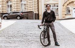 Hombre joven con una bicicleta en una calle de la ciudad Fotos de archivo libres de regalías