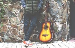 Hombre joven con una guitarra cerca de la pared de la piedra Imágenes de archivo libres de regalías