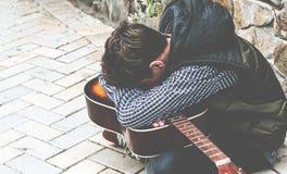 Hombre joven con una guitarra cerca de la pared de la piedra Imagen de archivo libre de regalías