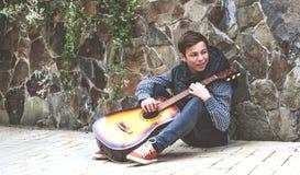 Hombre joven con una guitarra cerca de la pared de la piedra Foto de archivo