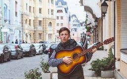 Hombre joven con una guitarra en la calle Fotografía de archivo libre de regalías