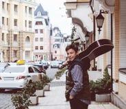 Hombre joven con una guitarra en la calle Foto de archivo libre de regalías