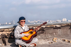 Hombre joven con una guitarra en un tejado de la casa Imagen de archivo