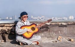 Hombre joven con una guitarra en un tejado de la casa Fotos de archivo libres de regalías