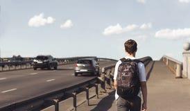 Hombre joven con una mochila que camina en un puente Imagen de archivo libre de regalías