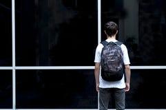Hombre joven con una mochila que mira en una ventana de cristal Fotos de archivo libres de regalías