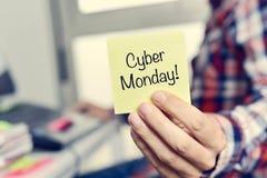 Hombre joven con una nota pegajosa con el texto lunes cibernético Imagen de archivo libre de regalías