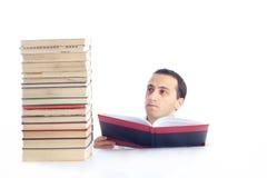 Hombre joven con una pila de libros que lee uno de ellos Imagenes de archivo