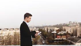 Hombre joven con una tableta en el tejado de una casa alta Imagenes de archivo