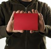 Hombre joven con una tarjeta vacía roja Imágenes de archivo libres de regalías