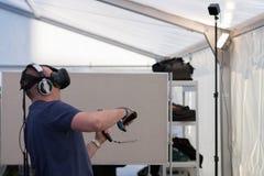 Hombre joven con VR - los vidrios y los reguladores juegan al juego Foto de archivo
