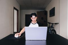 Hombre joven concebido que mira un ordenador portátil mientras que trabaja en casa Fotografía de archivo