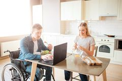 Hombre joven concentrado en el funcionamiento de la silla de ruedas con el ordenador port?til y la ensalada de la consumici?n El  fotos de archivo