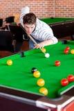 Hombre joven concentrado que juega el billar Imagen de archivo libre de regalías
