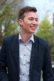 Hombre joven confiado en la chaqueta azul, sonriendo al aire libre Imagen de archivo libre de regalías
